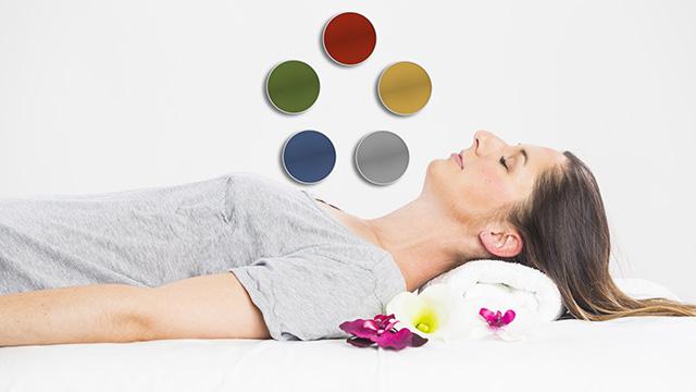 Eine Klientin liegt auf ihrem Rücken. Über ihrem Körper ist der Farbkreis der 5 Elemente aus der Kinesiologie zu sehen.