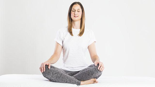 Eine Klientin sitzt im Schneidersitz. Sie hält ihre Augen geschlossen um ihre Sinne zu schärfen. Dafür führt sie Übungen aus dem Bereich der Kinesiologie durch.