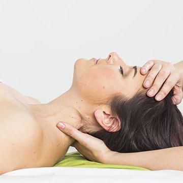 Die Klientin liegt am Rücken. Die Kinesiologin stützt mit ihrer linken Hand den Nacken, während ihre rechte Hand auf der Stirn der Klientin ruht. Nacken und Kopf werden angenehm entspannt.
